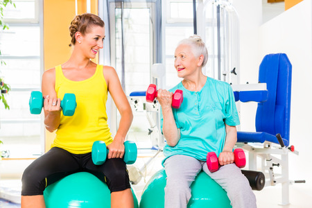 dumb bells: Senior and young woman on fitness ball doing sport having dumbbell workout in gym or health club