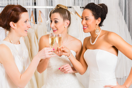 fitting in: Women drinking champagne while bridal gown fitting in wedding fashion store