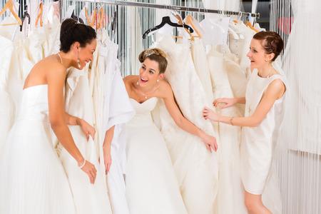 bridal gown: Mujeres que se divierten durante el montaje vestido de novia en la tienda de moda nupcial Foto de archivo