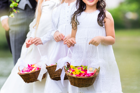 flower baskets: Wedding couple bride and groom with flower children or bridesmaid in white dress and flower baskets