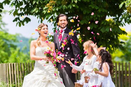 matrimonio feliz: Pares de la boda de la novia y el novio con ni�os de las flores o la dama de honor en el vestido blanco y cestas de flores