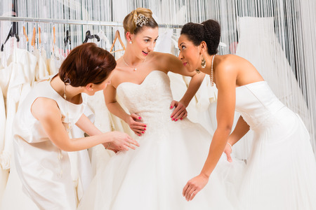 fitting in: Women having fun during bridal gown fitting in wedding fashion store