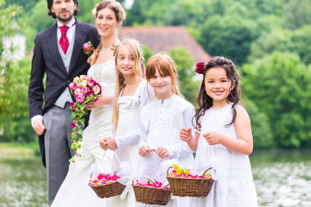Wedding couple bride and groom with flower children or bridesmaid in white dress and flower baskets
