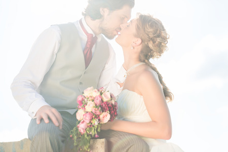 Bridal pair kissing on field after wedding photo
