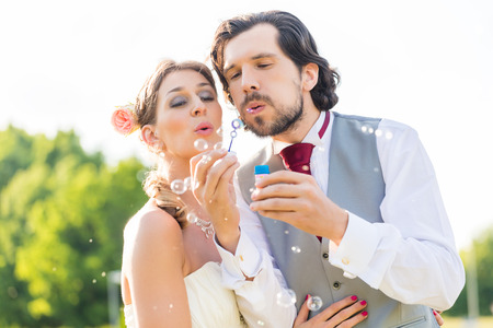 Wedding bride and groom blowing bubbles outside on field photo