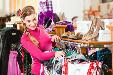 tracht: Traditional clothes - young woman is buying Tracht or dirndl in a shop