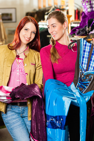 Traditional clothes - young woman is buying Tracht or dirndl in a shop with her friend photo