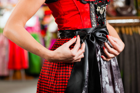 try on: Traditional clothes - young woman is buying Tracht or dirndl in a shop, she has to try it on before Stock Photo