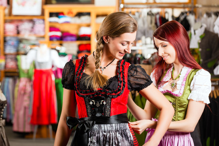 try on: Traditional clothes - young woman is buying Tracht or dirndl in a shop, she has to try it on before and a friend is tying the ribbon