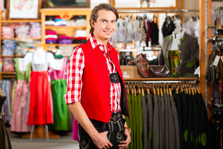 he is a traditional: Traditional clothes - young man is buying Tracht or lederhosen in a shop, he has to try it on before Stock Photo