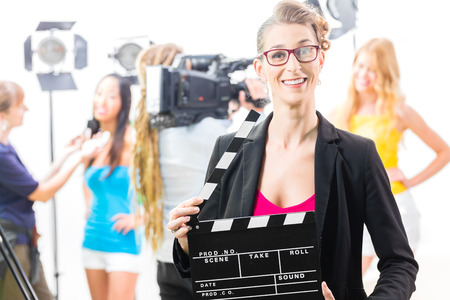 film shooting: Woman with take clap or board on Film Set of video production for TV, television, news or commercial
