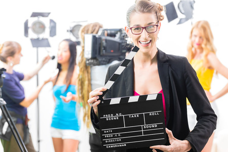 Woman with take clap or board on Film Set of video production for TV, television, news or commercial photo