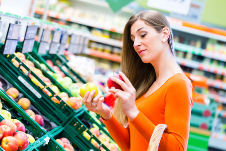 Woman selecting apples while grocery shopping in supermarket photo