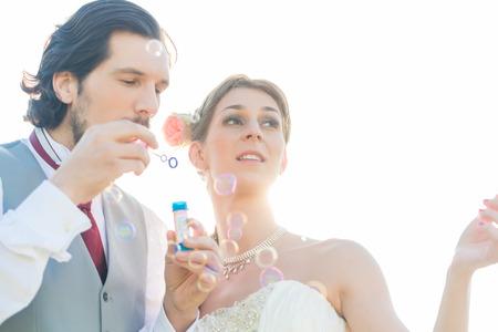burbujas de jabon: Pares de la boda soplando pompas de jab�n fuera Foto de archivo