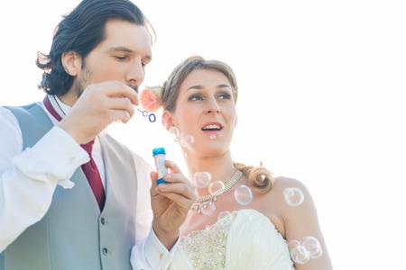 Wedding couple blowing soap bubbles outside photo