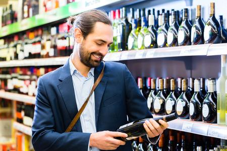 botella de licor: Hombre seleccionando vino en la tienda de licores