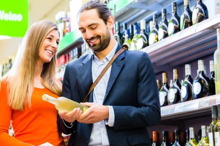 carro supermercado: Pareja de seleccionar el vino en el supermercado Foto de archivo