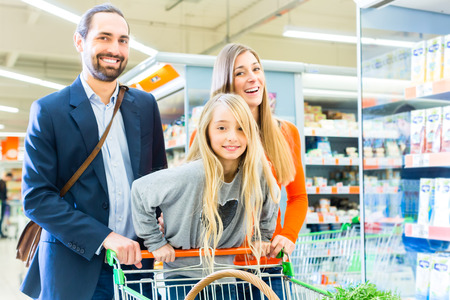 Family with shopping cart in supermarket store photo