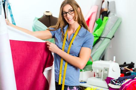Freelancer - Modedesigner oder Tailor Arbeit an einem Design oder Entwurf mit bunten Stoffen