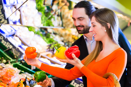 Couple selecting paprika while grocery shopping in supermarket photo