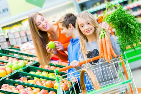 stores: Familie selecteren fruit en groenten, terwijl boodschappen in de supermarkt
