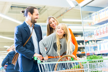 Family with shopping cart in supermarket store Stock Photo