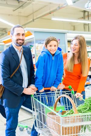 carretilla de mano: Familia con carrito de la compra en la tienda de comestibles