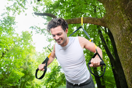 suspension: man exercising with suspension trainer sling in City Park under summer trees for sport fitness Stock Photo