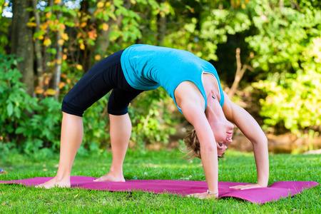 Young woman in city park doing yoga or warming up for exercising photo
