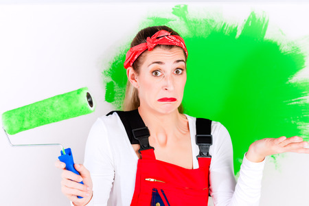 wrong: Woman at home improvement give up painting wall with wrong colour Stock Photo