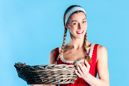 Woman in Dirndl or Bavarian traditional costume wearing wicker basket photo