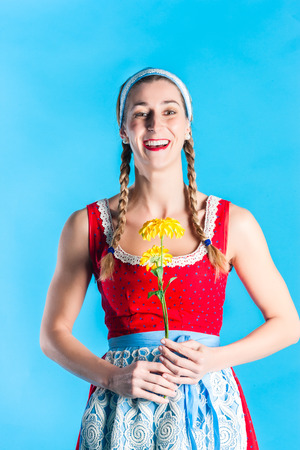 Woman in dirndl dress holding flowers photo