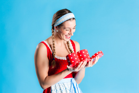 Woman in dirndl dress opening gift or present photo