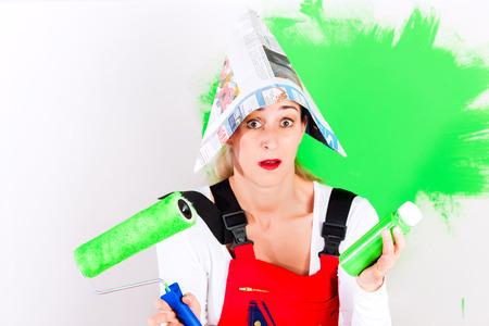 amateur: Mujer que se divierte en la pared de la pintura mejoras para el hogar con el color verde y el pincel
