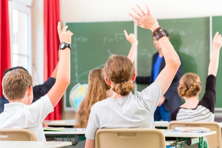 School class teacher giving lesson in front of a blackboard or board teaching students or pupils, they are raising their hands as they know all the answers Banque d'images
