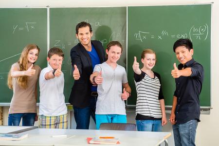 clase media: Educación escolar - Profesor y estudiantes de pie delante de una pizarra con el trabajo de matemáticas en un aula o clase Foto de archivo