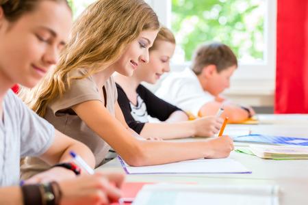 Los estudiantes o alumnos de clase de la escuela que escriben una prueba de examen en el aula para concentrarse en su trabajo