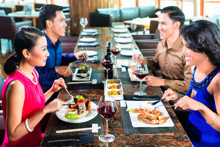 adult indonesia: Asian Friends eating and drinking wine in restaurant
