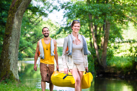 carrying: Man and woman carrying canoe to forest river