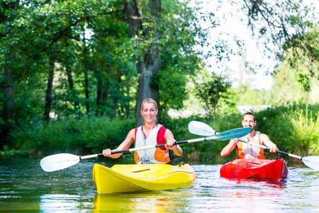 piragua: Amigos remando con canoa en el río del bosque