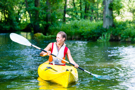 paddling: Woman paddling with canoe on forest river Stock Photo