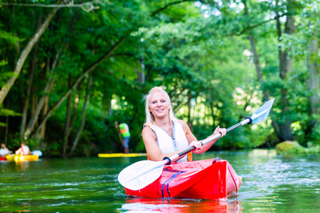 jacked: Woman paddling with canoe on forest river Stock Photo