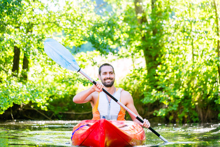 jacked: Man paddling with kayak on river for water sport