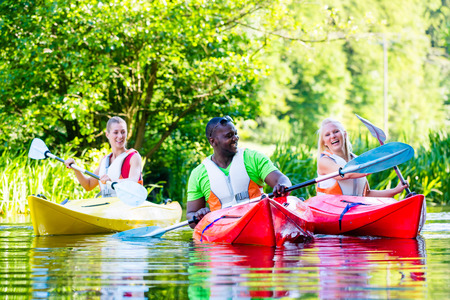 jacked: Friends paddling with canoe on forest river