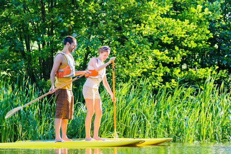 sup: Friends paddling with surfboard sup on forest river Stock Photo
