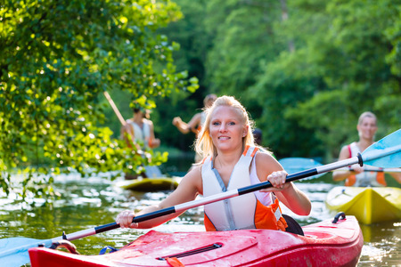 jacked: woman with kayak or canoe on forest river Stock Photo