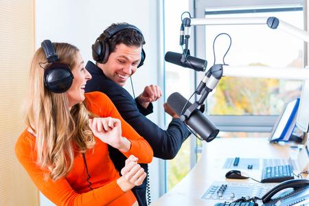 Presentatoren of moderators - man en vrouw - in radiostation hosting-show voor radio wonen in Studio Stockfoto