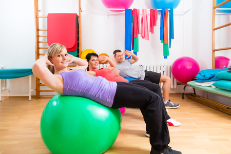 stretches: Patients at the physiotherapy doing physical exercises with therapist on training balls