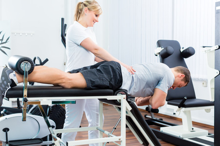 Patient at the physiotherapy doing physical exercises with therapist with sport doctor Stockfoto