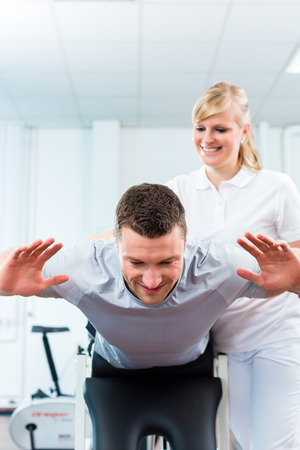 medicate: Patient at the physiotherapy doing physical exercises with therapist with sport doctor Stock Photo